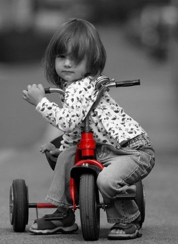 girl in black and white sitting on red trike